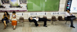 A man lies across several benches inside the Osaka subway station.
