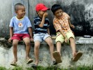 Three Indonesian boys share a laugh during a summer day in Banda Aceh, Indonesia.  Image taken from the book,