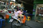 Two kids sit atop a motorbike in Bangkok.