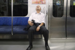 A man sleeps under a Japnese ice cream ad on the Tokyo subway.