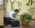 After heavy drinking, a man vomits into a potted plant inside the Nishi Funabashi Station.