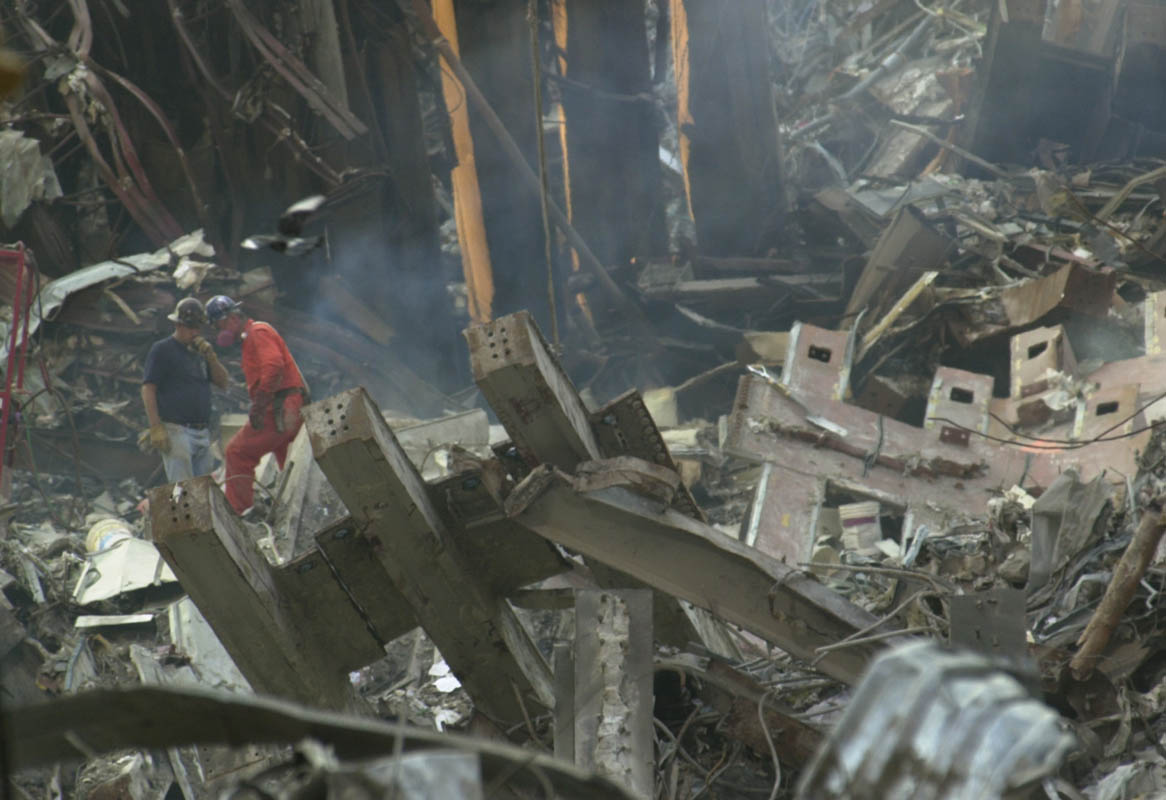 Rescue workers walk across the collapsed remains of one of the twin towers at the World Trade Center complex in New York City