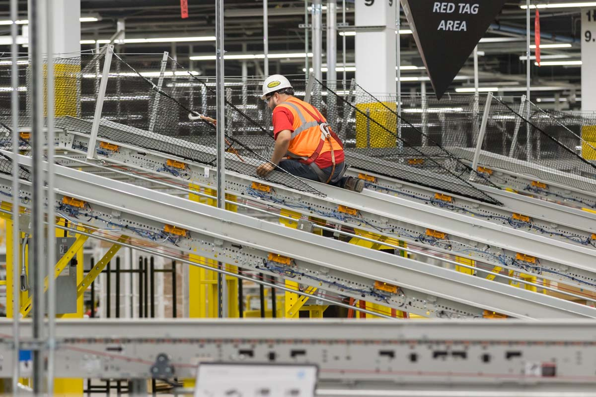 Workman working on conveyor system at the new Amazon Fulfillment Center, in West Deptford, NJ on 8/17/18.