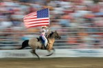 A rider carries the American flag during opening ceremony at the Cowtown Rodeo in Woodstown, New Jersey