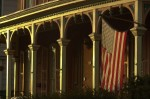 An American flag hangs from the front porch of a house as the sun sets in Hunterdon County, New Jersey.