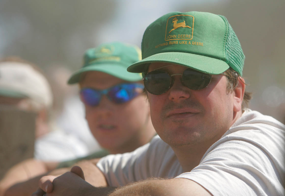 Two men wearing John Deere hats watch the farm tractor pulls at the Hunterdon County 4-H Fair in East Amwell Township