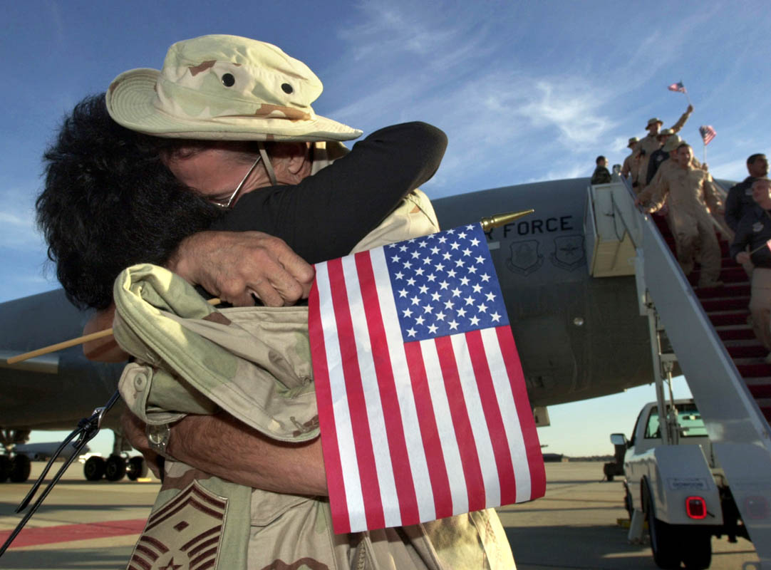 WELCOME HOMEAs Air Force reservists file off a KC10 Aerial Tanker, a soldier hugs his wife after the 514th Air Mobility Wing returned from military service, at McGuire Air Force Base in Wrightstown, New Jersey