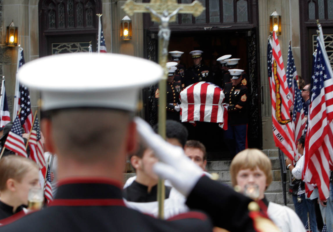 A Marine salutes the casket during a funeral for a fallen Marine.