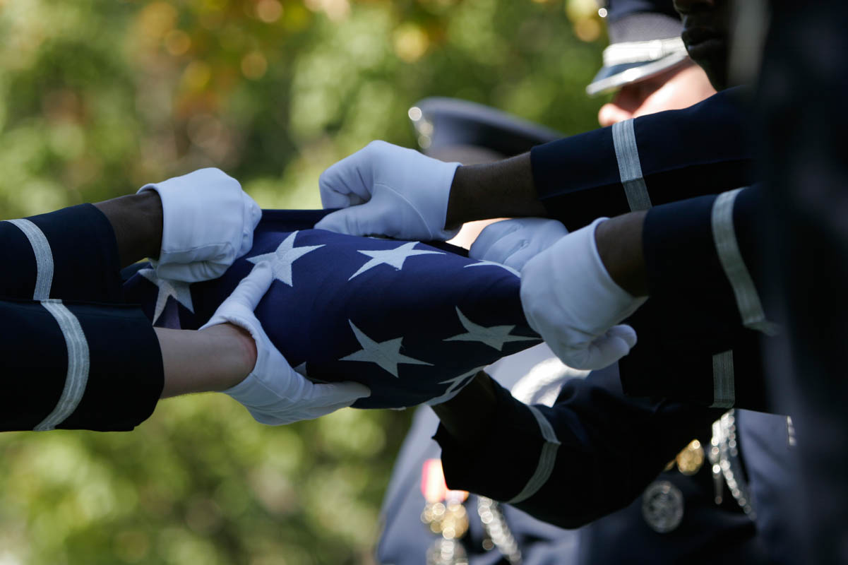 Members of the Honor Guard fold an American flag during burial ceremony for a fallen soldier at Arlington National Cemetery in Arlington, Virginia