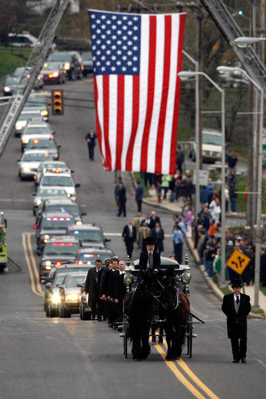 A horse drawn hearse leads the funeral procession for a fallen FBI agent into the Highland Memorial Cemetery  in Pottstown, Pa