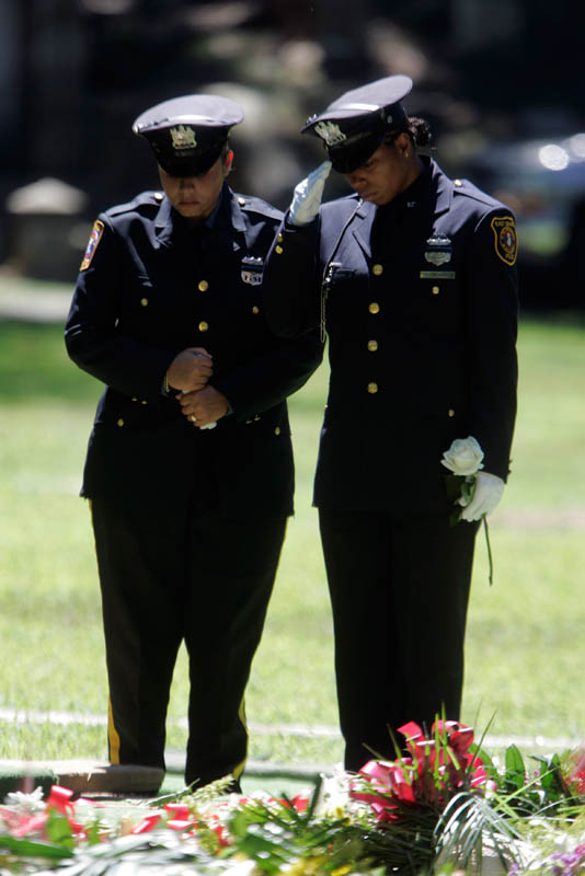 Two police officers stand over the grave  after funeral for a fallen police officer at Rosedale Cemetery in Orange, New Jersey