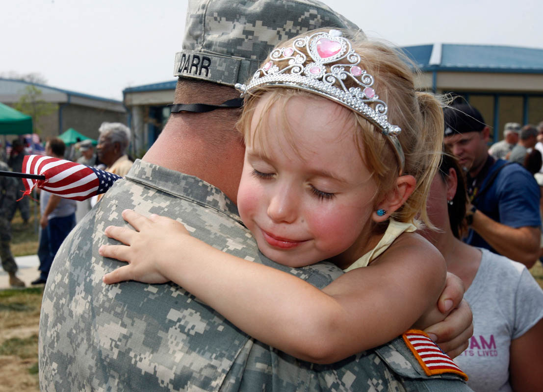 A young girl hugs her daddy on his return from duty in Iraq, at Fort Dix in Wrightstown, New Jersey