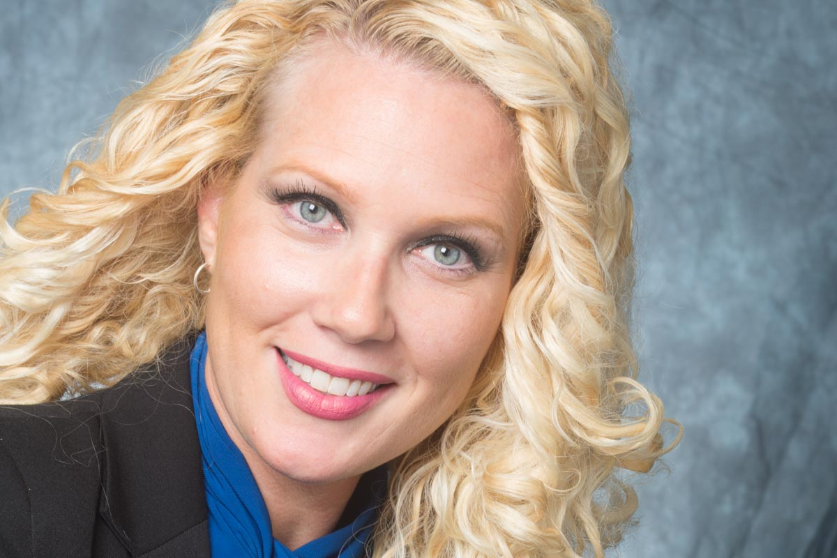 Headshot of blonde haired female executive in the education industry.