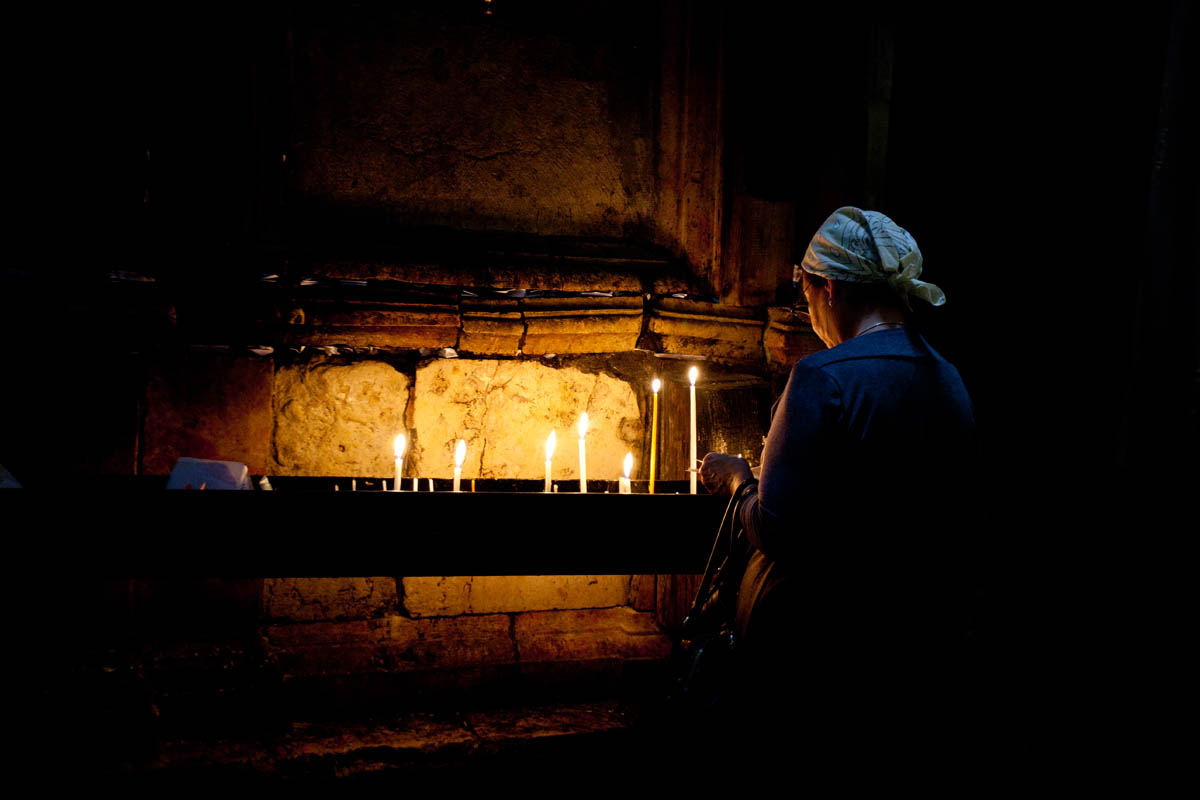 A woman lights a candle in the Church of the Holy Sepulchre in Jerusalem.