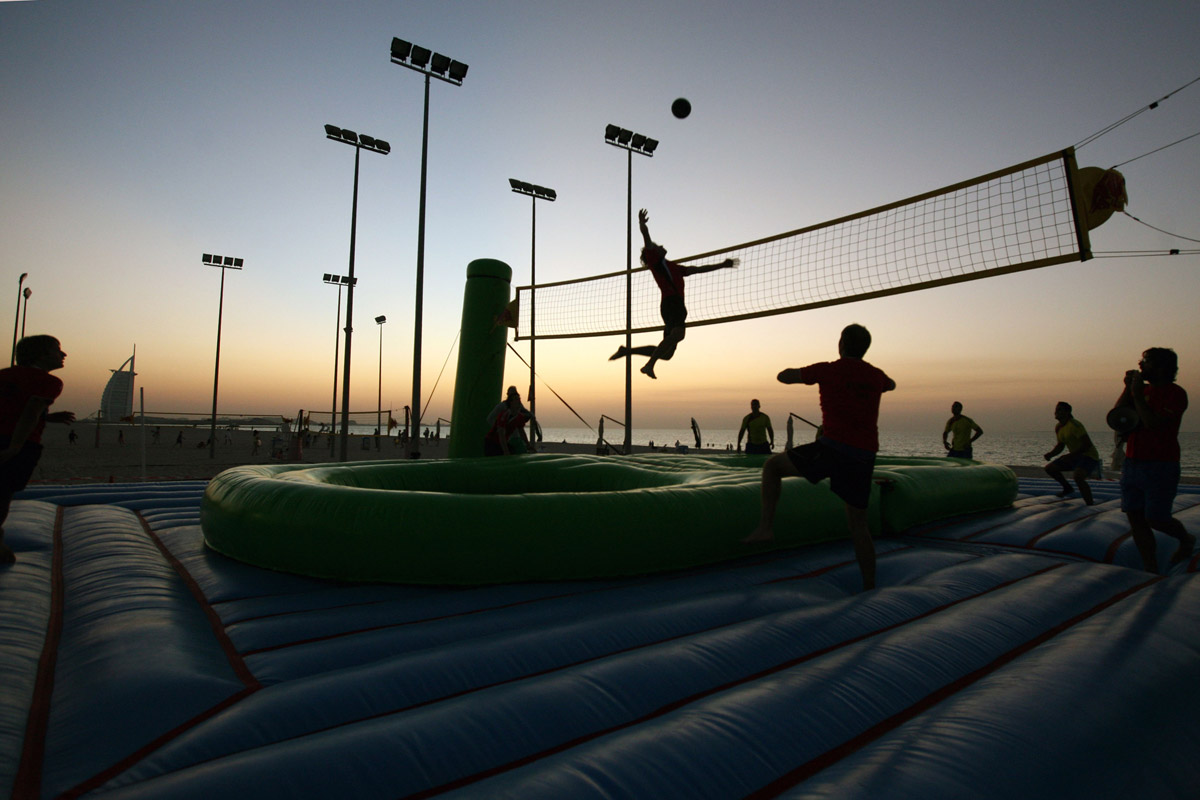 Players from Brazil and the Netherlands in action during a bossaball match, a new sport which started in Brazil, played on an inflatable court with a trampoline to bossa music, at the beach in Dubai on November 26, 2009.