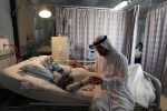 Syed Muhammad Amroze sits with his wife Hussanzari, 46 years old, while she undergoes dialysis treatment at the Qassimi hospital in Sharjah on May 18, 2010.