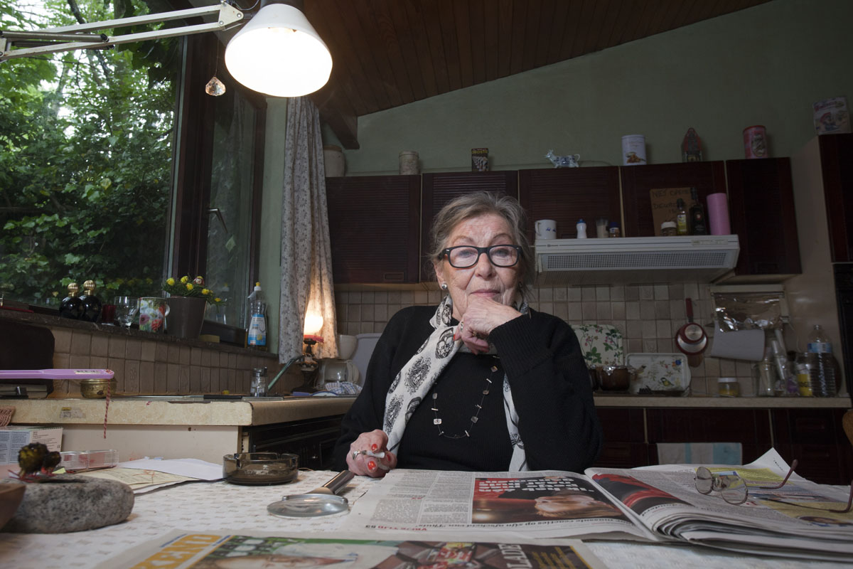 DOEL, BELGIUM - May 11:  Emilienne Driesen, pictured in her home in the village of Doel, on May 11, 2014.  The 80-year-old is known as The Angel of Doel, and is one of 25 remaining residents in the village and has lived there her entire life. The 400-year-old village is wedged between a nuclear power station and the ever-expanding Port of Antwerp. Many villagers left in the late 1990s when the regional government outlined plans to expand the port and residents were offered premiums to sell their homes. Once having had a population of around 1,300, it is now home to a mere 25 occupants who refuse to leave. An initiative, Doel 2020, has been established by the remaining inhabitants to fight the proposed port expansion and subsequent demolition of the village, the deadline for which is set for 2020, but the outcome remains uncertain. After years of neglect, squatting, looting, and uncertainty, this modern-day ghost town is a haven for street artists who have turned the dilapidated houses into a colourful open-air gallery attracting urbex photographers and the curious alike.