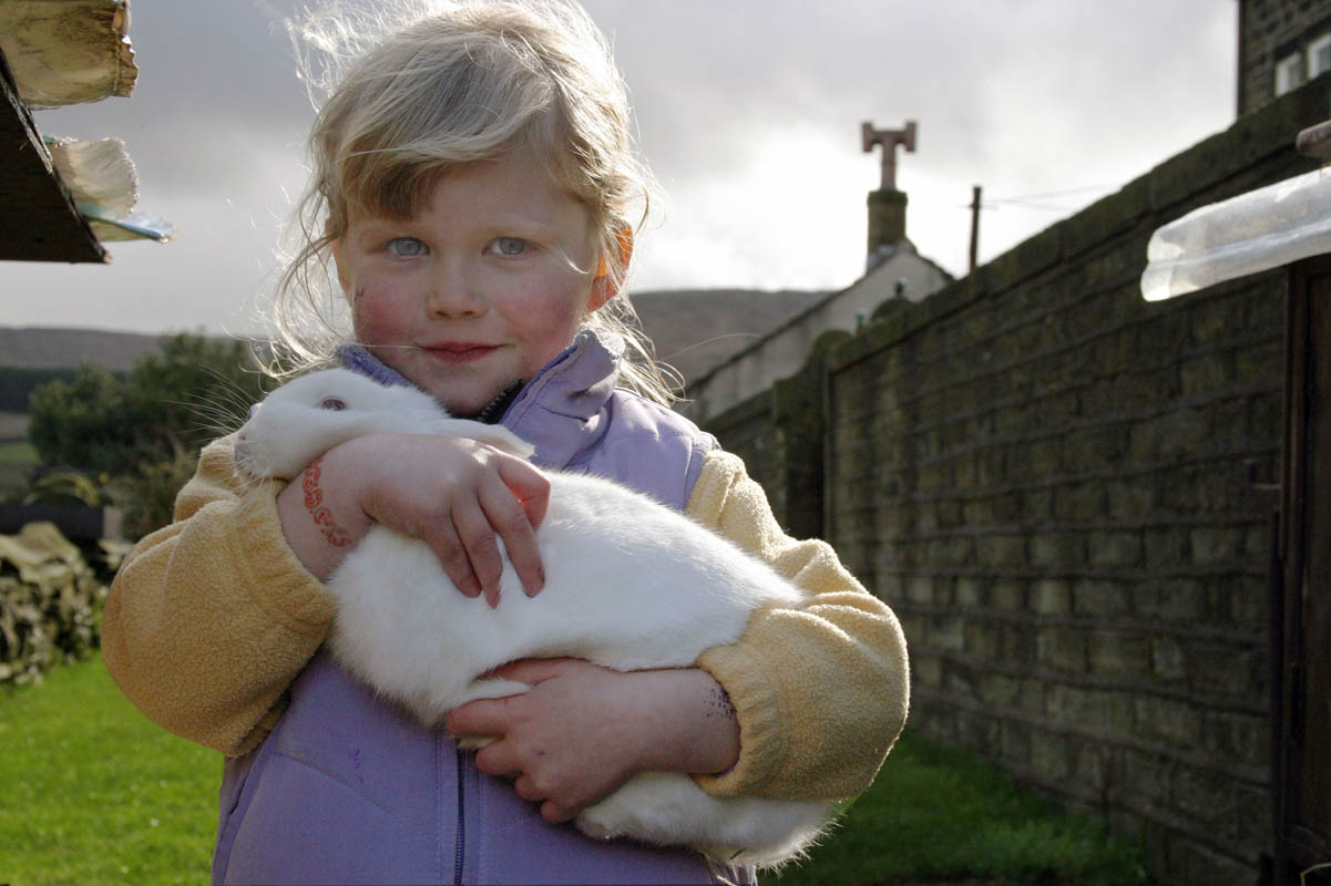 Portrait of a farmer's daughter during lambing season in the Holme Valley, West Yorkshire, England.
