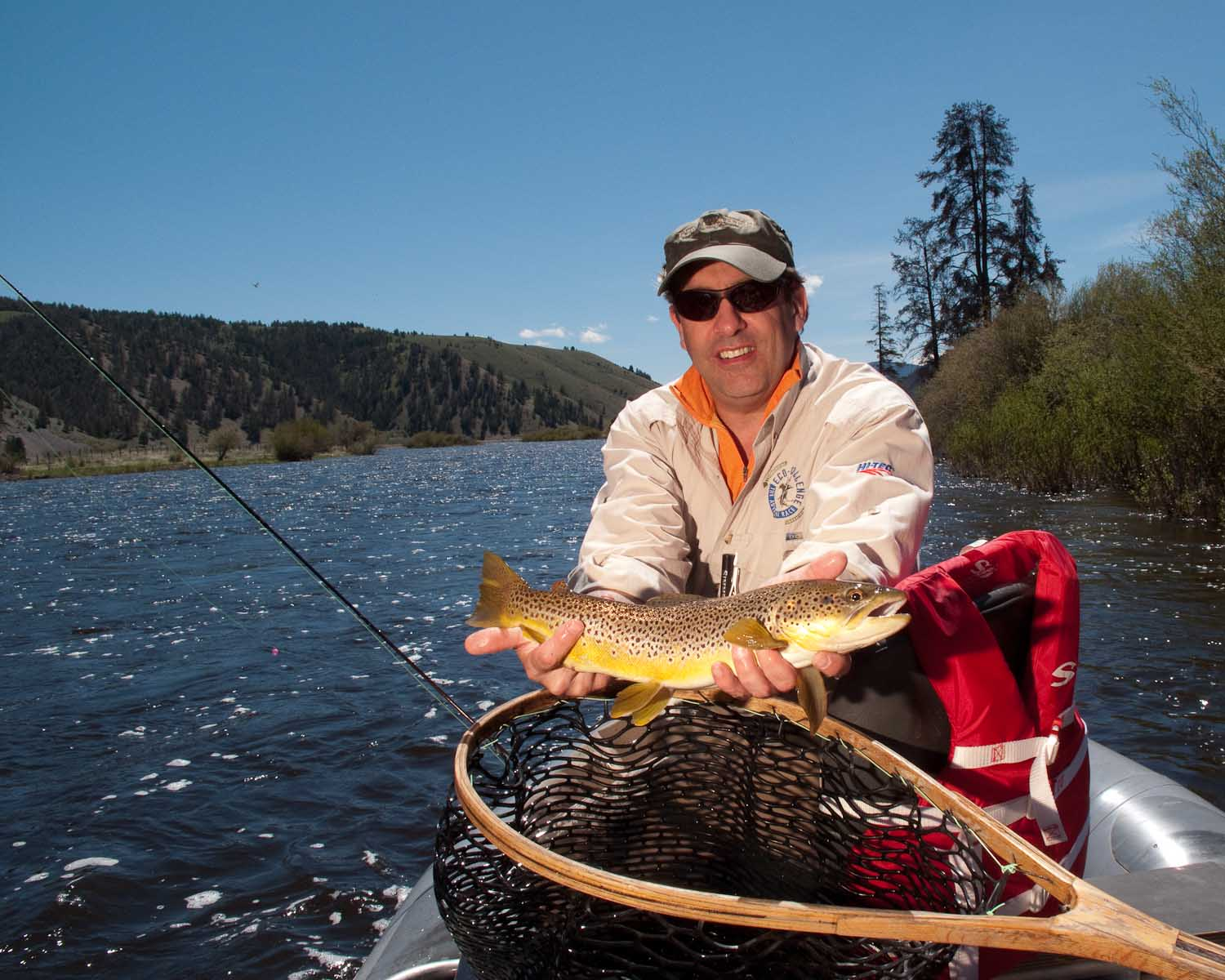 Happy flyfisher with a big, fat brown trout, caught on a dry fly from the Big Hole River.