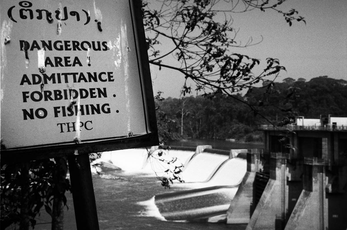 A sign from the dam company warning about no fishing and danger in the area near the dam.