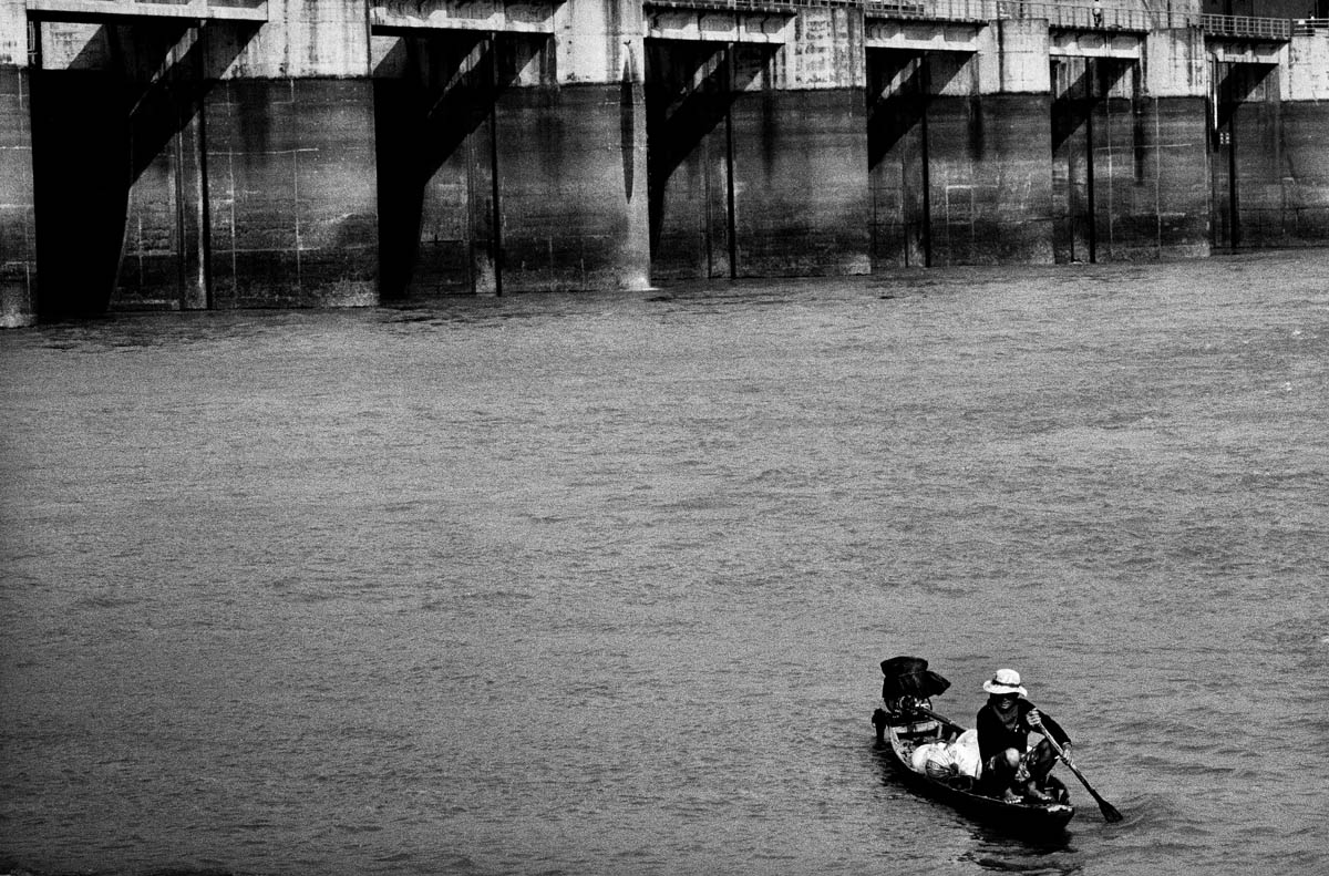 A fisherman in his boat on the day of the closing of the gates. For the next couple of days the area upriver from the dam gets filled with fish because the dam blocks their migration downstream to the Mekong.