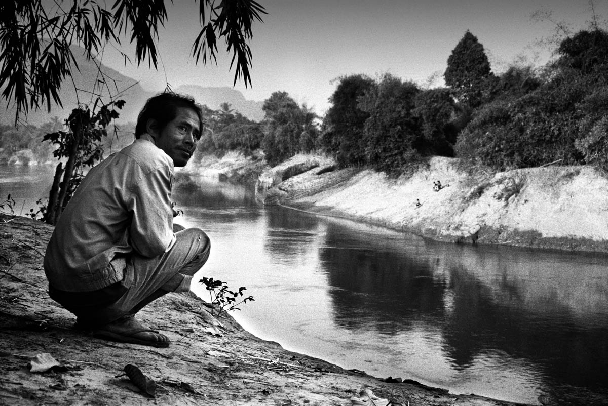 A villager waiting to transport school children across the river in his boat. The promised bridge has never been built and the strong currency and improvised floodings have made this a dangerous crossingpoint for children going to school. So far at least five children have been reported drowning at this point of the river.