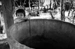 A boy leaning on to an empty well created to provide clean water to the village.