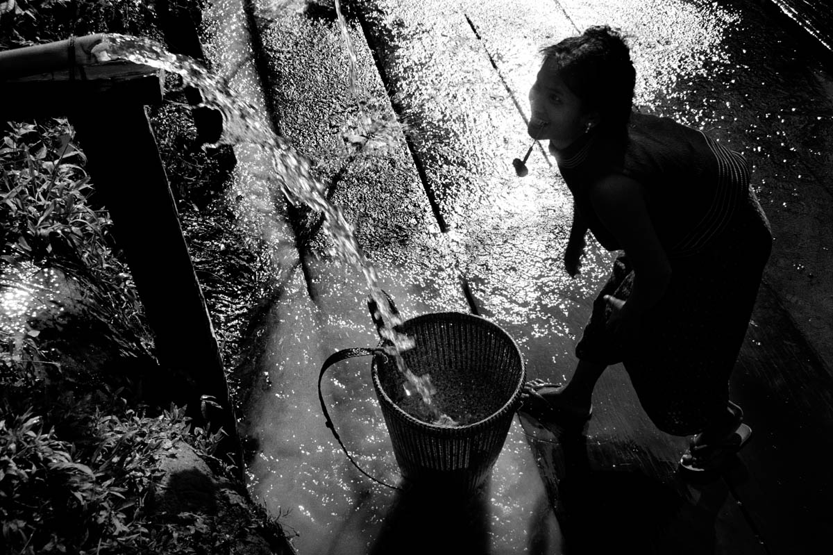 A woman cleaning rice. Her village has been relocated up in the hills far away from the original setting near the Se San river.