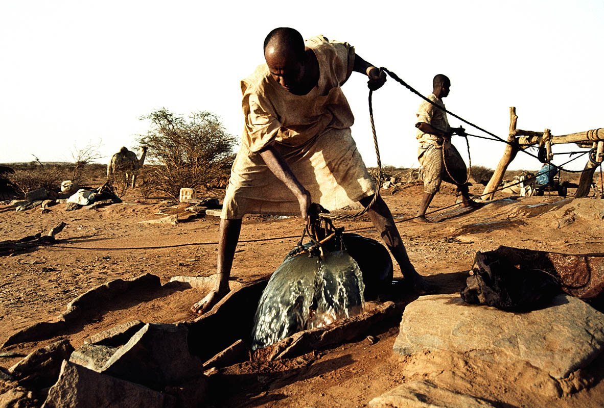 Nomads collecting water in a traditional way from a well in the desert.