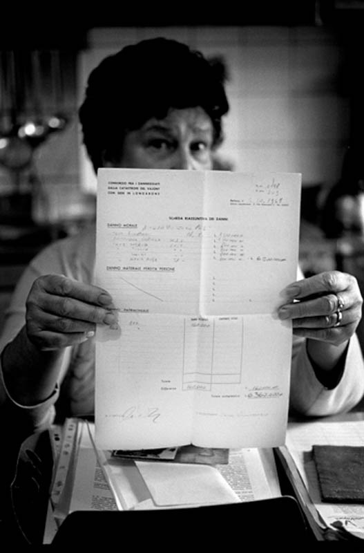 Carolina Teza demonstrating the {quote}invoice{quote} of the compensation given to her husband for the loss of his parents and four brothers and sisters. Only 20 years old he was obligated to accept a compensation of 3000 euro, but he has never recieved any psycological help. Carolina is still fighting today for an official aknowledgement for a foreseen tragedy.