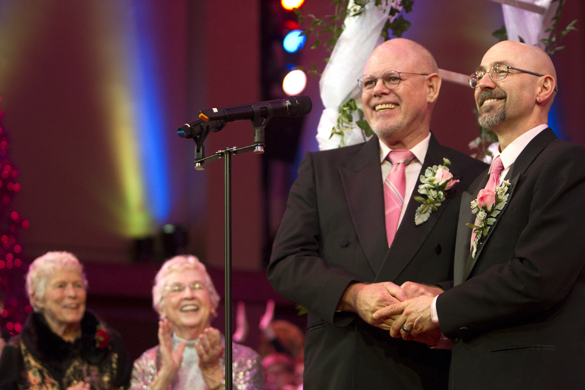Donald Jenny (left) and Neil Hoyt, from Bellevue, Wash., who have been romantic partners for 23 years, get married during the Seattle Men's Choir Holiday Concert in Seattle, Wash., on December 9, 2012.  {quote}It's overwhelming,{quote} said Hoyt. {quote}It's the biggest and best wedding party I can ever imagine.{quote} Jane Abbott Lighty, left, and Pete-e Petersen, from Seattle, behind them, also wed. They've been romantic partners for 35 years and received the first same-sex marriage license in Washington state after voter's approved to make it legal. {quote}I just can't believe this is happening after all these years,{quote} said Peterson. (© Karen Ducey 2012)