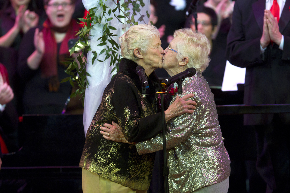 Jane Abbott Lighty, left, and Pete-e Petersen, from Seattle, get married during an interlude in the Seattle Men's Chorus Holiday Concert in Seattle, Wash., on December 9, 2012. Lighty and Peterson, who have been romantic partners for 35 years received the first same-sex marriage license in Washington state after voter's approved to make it legal. {quote}I just can't believe this is happening after all these years,{quote} said Peterson. (© Karen Ducey 2012)