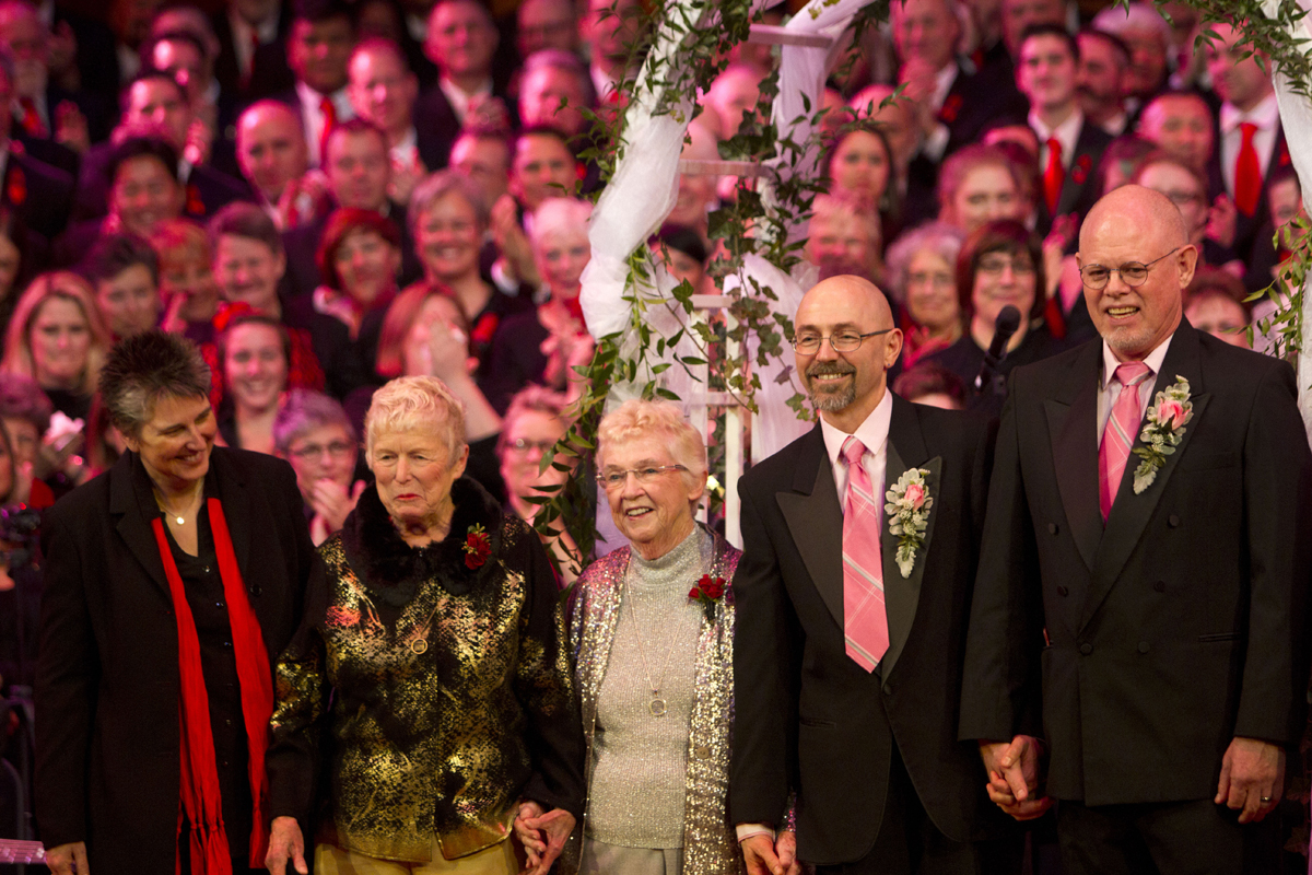 From left to right: Newlyweds Jane Abbott Lighty & Pete-e Petersen, from Seattle, and Donald Jenny (left) and Neil Hoyt, from Bellevue, Wash., face an audience of thousands during the Seattle Men's Chorus Holiday Concert/Wedding Celebration in Seattle, Wash., on December 9, 2012. Lighty and Peterson, who have been romantic partners for 35 years received the first same-sex marriage license in Washington state after voter's approved to make it legal. {quote}I just can't believe this is happening after all these years.{quote} said Peterson.  Also, tying the knot is Donald Jenny (left) and Neil Hoyt, from Bellevue, Wash., who have been partners for 23 years.  {quote}It's overwhelming.{quote} said Hoyt {quote}It's the biggest and best wedding party I can ever imagine.{quote}  Judge Anne Levinson oversaw the service. (© Karen Ducey 2012)