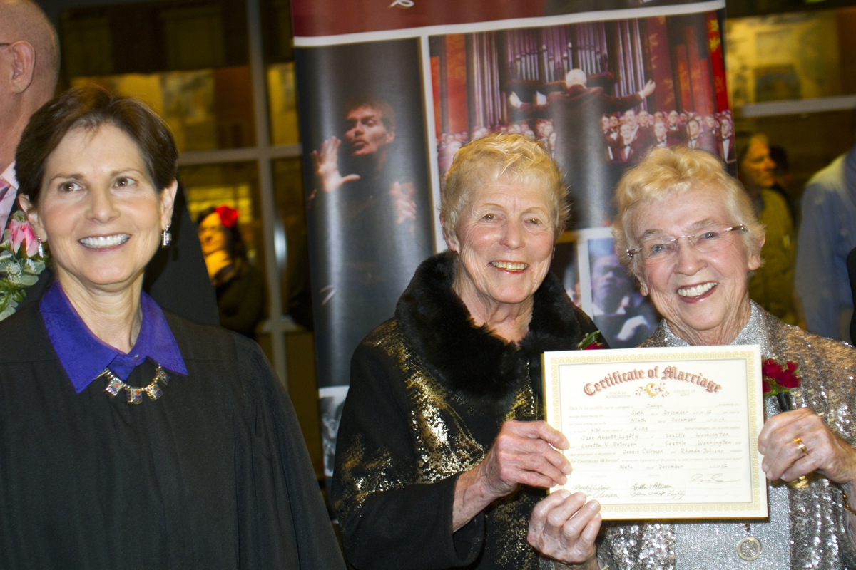 Jane Abbott Lighty, center, and Pete-e Petersen (right), from Seattle, hold up their marriage certificate overseen by  Judge Anne Levinson after their wedding ceremony at the Seattle Men's Chorus Holiday Concert in Seattle, Wash., on December 9, 2012. Lighty and Peterson, who have been romantic partners for 35 years received the first same-sex marriage license in Washington state after voter's approved to make it legal. {quote}I just can't believe this is happening after all these years,{quote} said Peterson.  (© Karen Ducey 2012)