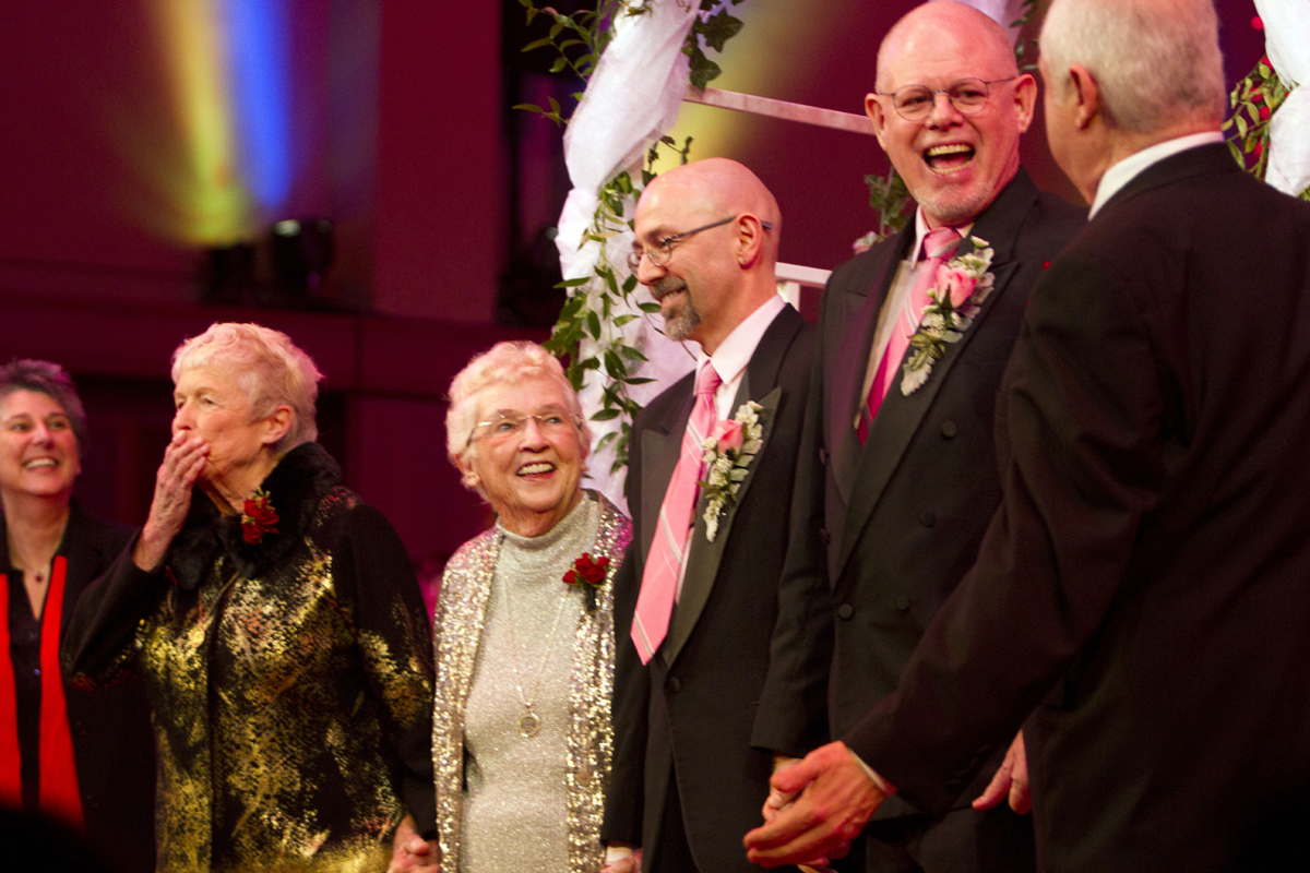 From left to right: Jane Abbott Lighty, Pete-e Peterson, Donald Jenny and Neil Hoyt, receive applause from the crowd after their wedding ceremony during the Seattle Men's Chorus Holiday Concert / Wedding Celebration in Seattle, Wash., on December 9, 2012. Lighty and Peterson, who have been romantic partners for 35 years received the first same-sex marriage license in Washington state after voter\'s approved to make it legal. {quote}I just can't believe this is happening after all these years.{quote} said Peterson. Says Hoyt {quote}It's overwhelming. It's the biggest and best wedding party I can ever imagine.{quote}  (© Karen Ducey 2012)