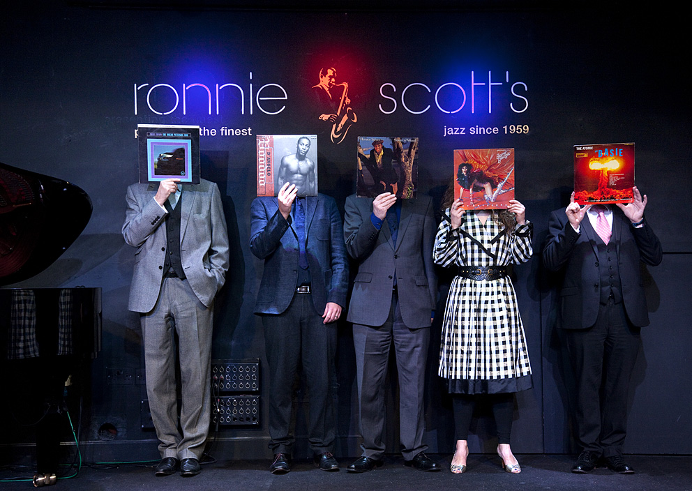 Ronnie Scott's is one of the world's most famous, renowned and respected music venues. This massively talented music booking team at the sharp-end of programming the iconic club are, of course, dedicated to the music, and to the business of building on a unique heritage and brand that dates back to the year that Miles Davis released 'Kind of Blue'.Though their roles are diverse, James, Nick, Paul, Sarah and Simon have one big thing in common – a deep passion for music. Each has shared a favourite recording as their 'One LP'.  In the image and text, they offer an insight into an album that they love, and share with us something of what inspires them to do what they do.Your One LP- by William EllisOne LP is a unique international project – to participate is an exciting and engaging experience, but one with a serious point and of significant personal value.Like Ronnie's, you can commission a One LP session for your music company to demonstrate to your customers and clients the elemental connection of your venture with its fundament – the music that both inspires and drives you and your colleagues to do what you do.Your portraits and short interviews could become a central element of your team's personal web profiles, promotional program, or as an innovative internal engagement activity. The session is relaxed, painless, fast and fun! The session at Ronnie Scott's took around 90 minutes including the interviews.Each One LP commission is unique, in addition to the portrait and interview there are a number of formats including a pop-up exhibition, a presentation on the project by its originator William Ellis - moreTo start planning your One LP Experience - email nowRonnie Scott's Jazz Club