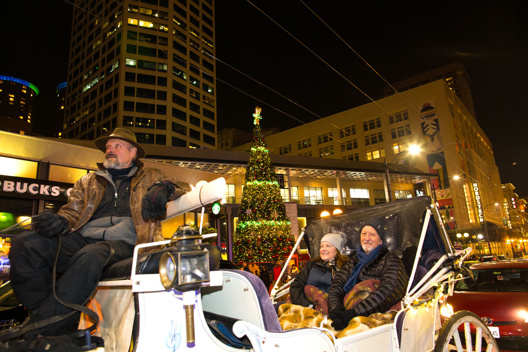 """""""He's all about making my dreams come true,{quote} Anita Emde says of her husband Mick Emde, both from Redmond, WA.  {quote}I've always wanted to be in a horse-drawn carriage."""" The two enjoy a horse and carriage ride around the Westlake Center area in Seattle, WA on December 9, 2017. """"It was romantic. It was warm. He provided a nice blanket,"""" she says. (© Karen Ducey)"""