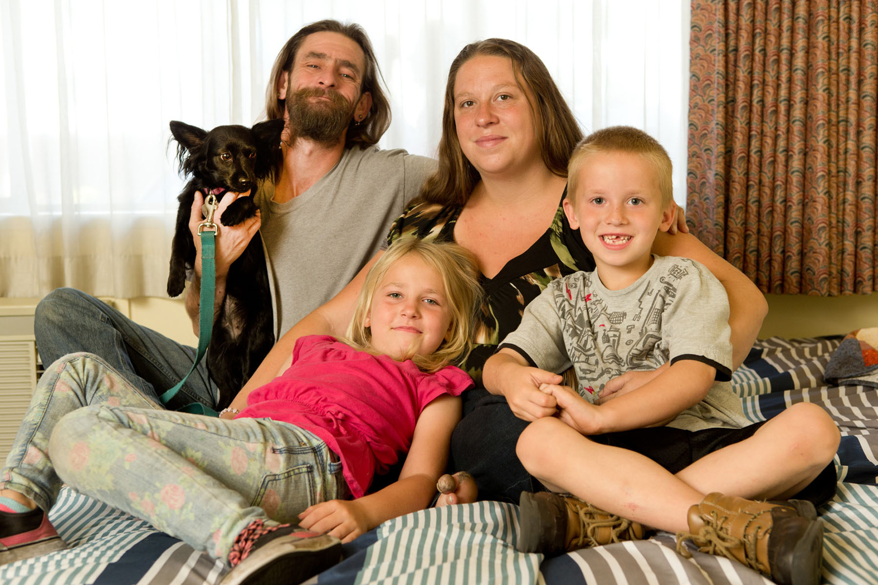 From left to right: J.D., Mary Delp, her two children Elijah Delp, 6, and Krystallynn Delp, 7, and one of their dogs, Tinkerbell, are photographed at Mary's Place the Guest Rooms in South Lake Union in Seattle, WA on June 23, 2016. The Guest Rooms provide transitional housing for families including those with pets. Delp says she wouldn't have come here if they didn't allow Tinkerbell and the family would be sleeping in the sleeping in their van. (photo © Karen Ducey Photography)