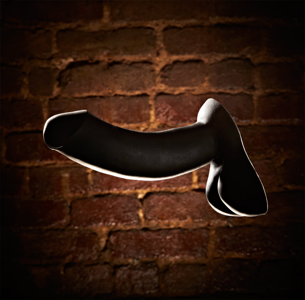 still life photograph of black dildo sex toy.