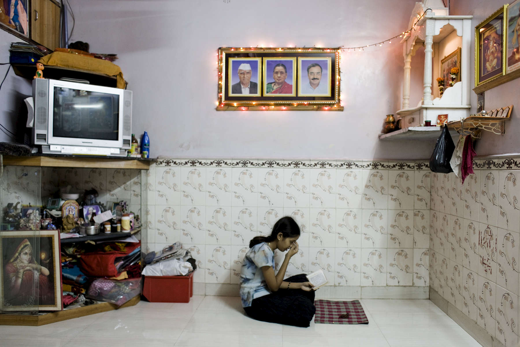 Namira, 16, prays in her house on the 6th floor of the building 53 in Lullubhai Compound, 17 November 2009.More than 60,000 people of any religious, live in this new kind of slum after their homes were demolished.