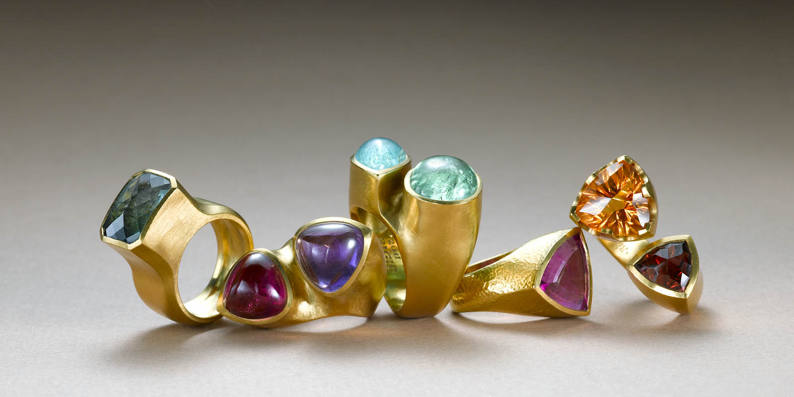 22 karat sculptured rings with afgani tourmaline, pink tourmaline and amethyst trillium cabs, green and blue paraiba tourmalines, rubelite shield, and carved citrine and garnet.