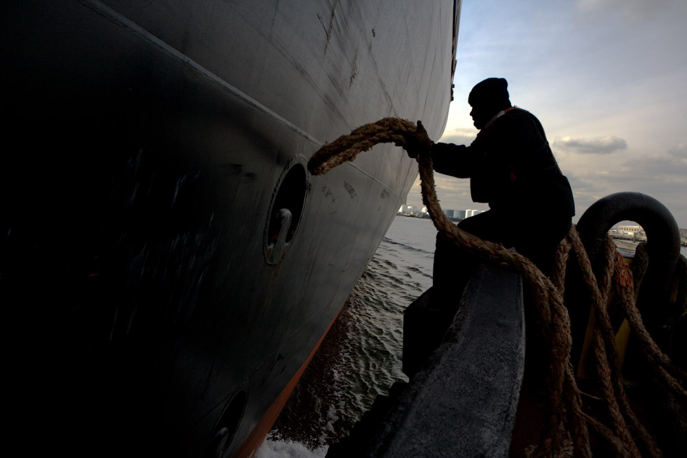 A deckhand on the McAllister Sisters ties the tugboat to a container ship in New York Harbor November 8, 2007 in New York City. McAllister Towing has been assisting ships dock in the Port of New York and New Jersey since 1864.