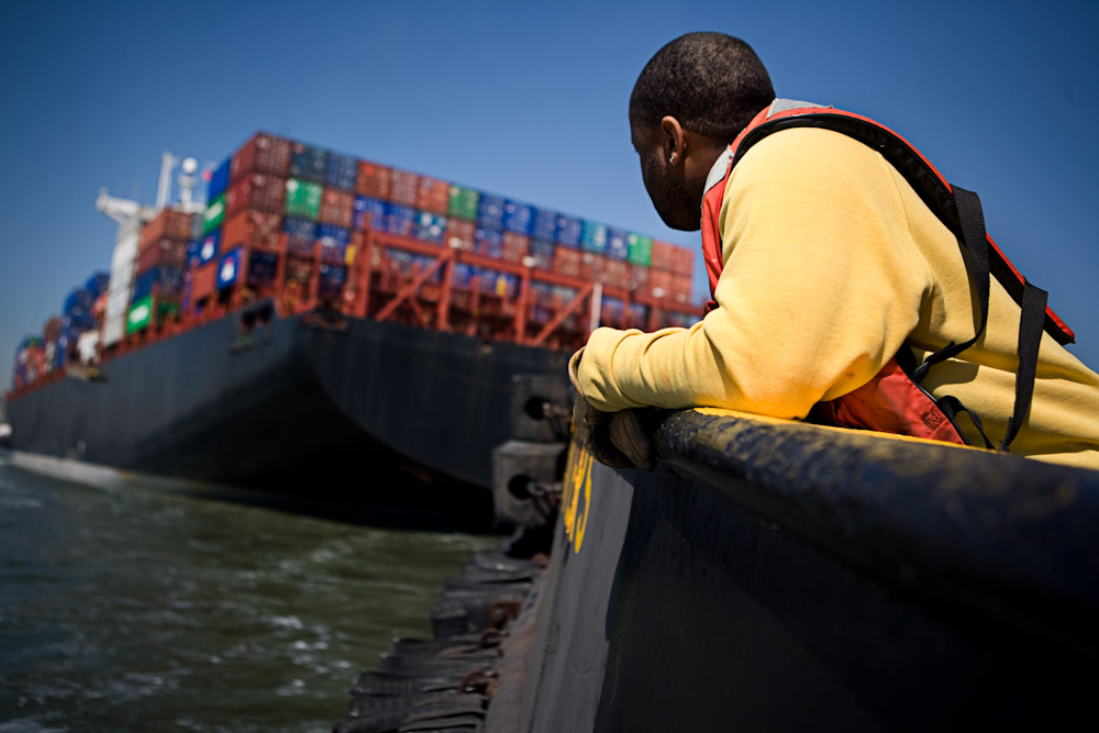 A worker on a tugboat watches as container ship moves through New York Harbor April 17, 2008 in New York City. Tugboats operate in New York Harbor 24 hours a day.