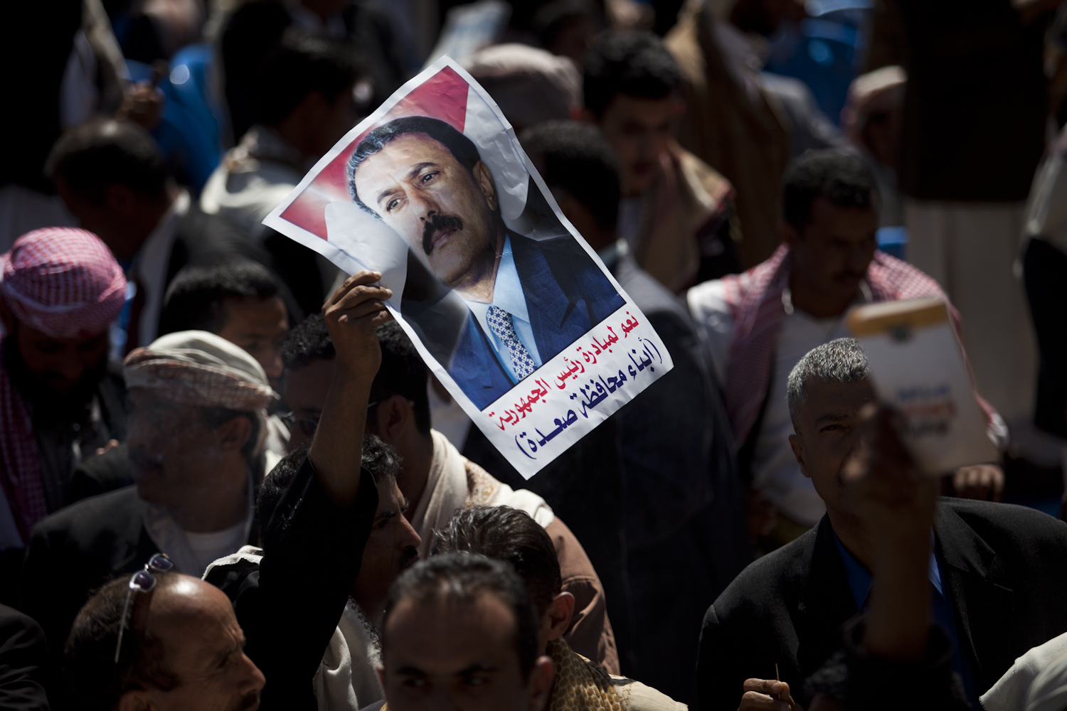A poster of President Ali Abdullah Saleh floats through a crowd in a stadium after the president gave a speech to thousands of supporters on March 10, 2011 in Sana, Yemen. Thousands of Yemenis have been protesting around the country calling for the ouster of President Ali Abdullah Saleh, who has been in power for 32 years.