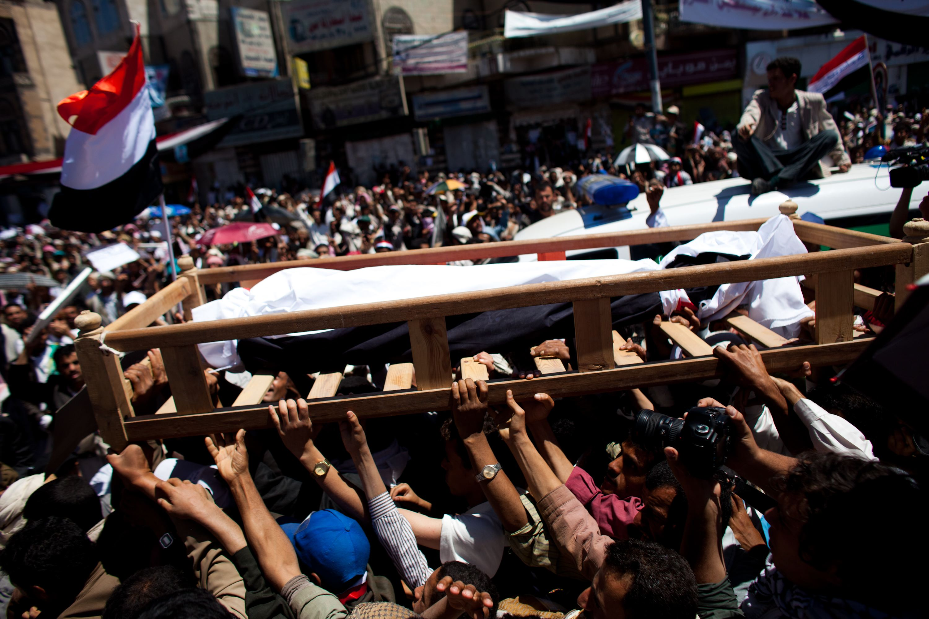The body of a man killed during clashes with police is moved to a stage during a memorial service at the anti-government protest site in front of the University of Sana on March 11, 2011 in Sana, Yemen. Thousands of Yemenis have been protesting around the country calling for the ouster of President Ali Abdullah Saleh, who has been in power for 32 years.