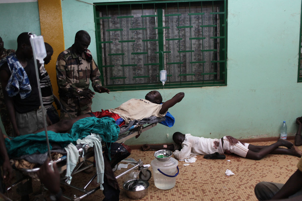 A wounded man,apparently a seleka is surronded by friends as he is waiting for treatment at the hopital communtaire.