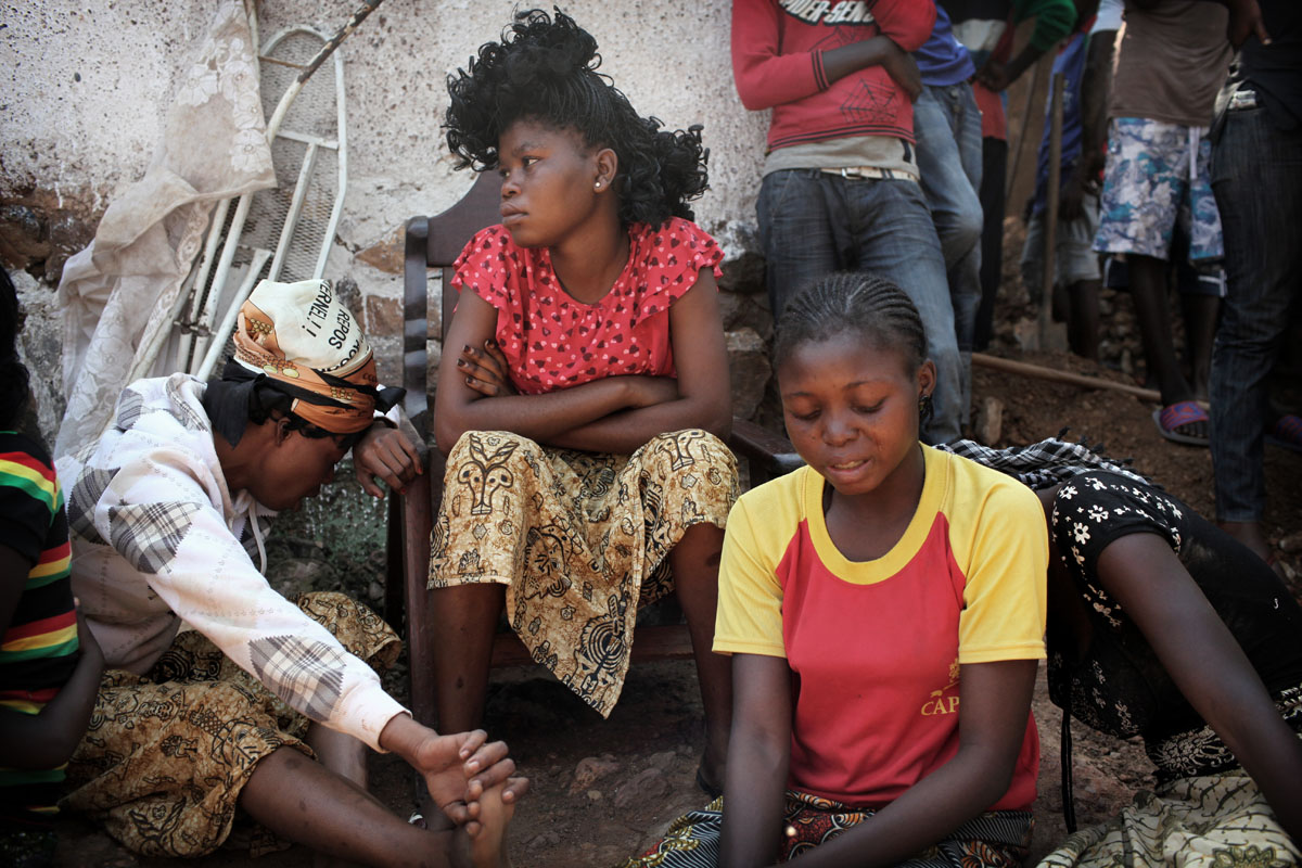 Girls mourn a Christian men from the Boyrabe neighborhood that has been found as he was trying to cross the street.he has beaten to death by selekas,according to his relatives.