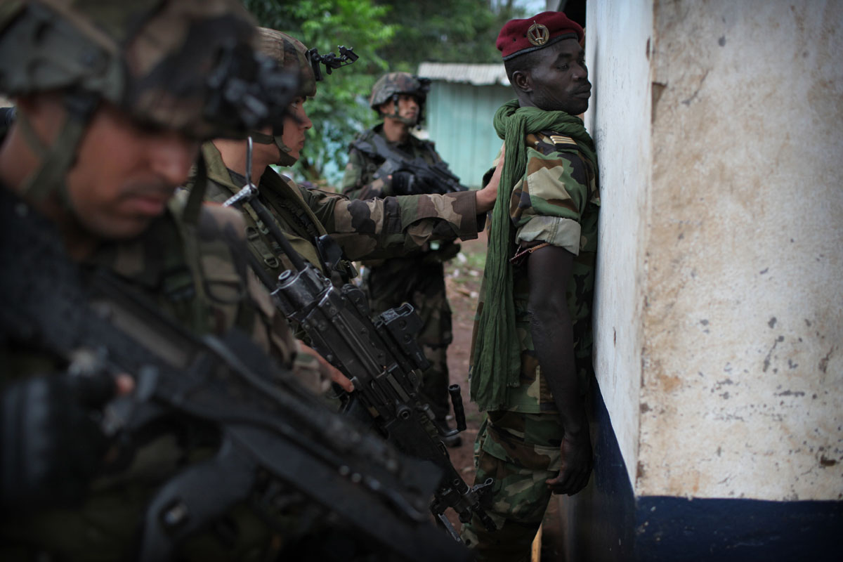 French soldiers control a Selaka soldier at PK12 checkpoint,at the entrance of Bangui.