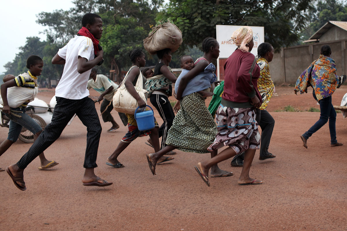 centrafrican people run away from fire exchange between anti balakas and seleka soldiers next to the Bangui airport.