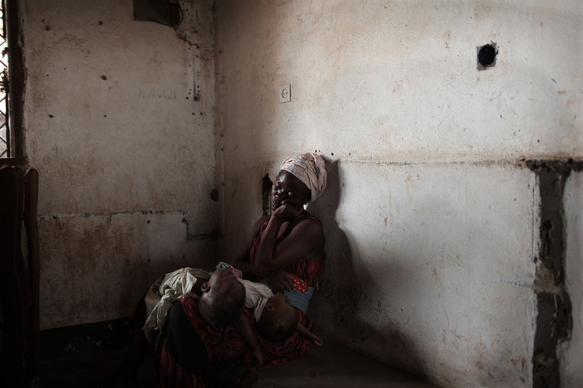 at the Pediatric center in Bangui, a woman waits with her child for treatment.